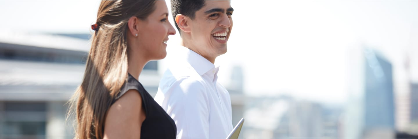 Man and woman standing by balcony smiling