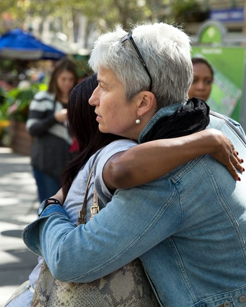 Two women serious and embracing