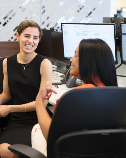Two women sitting at a workstation and smiling