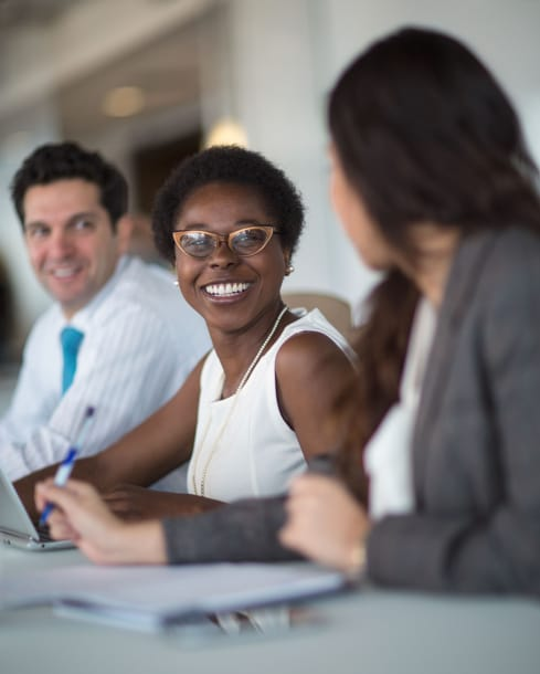 Woman sitting at table looking at coworker and smiling