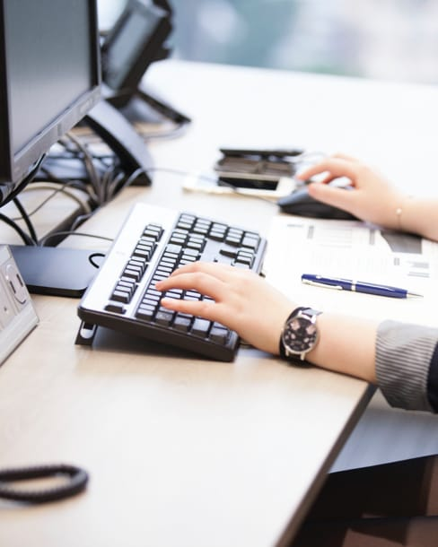 Woman at desk, focusing on hands on keyboard